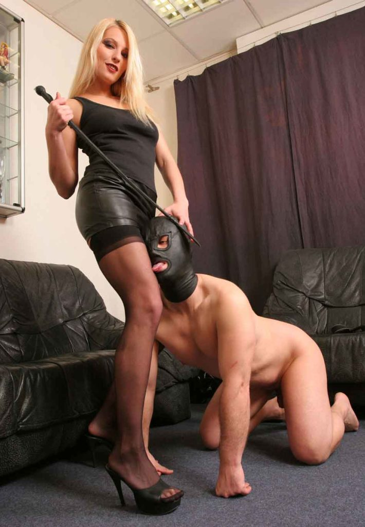a mistress in a black dress holding a sub
