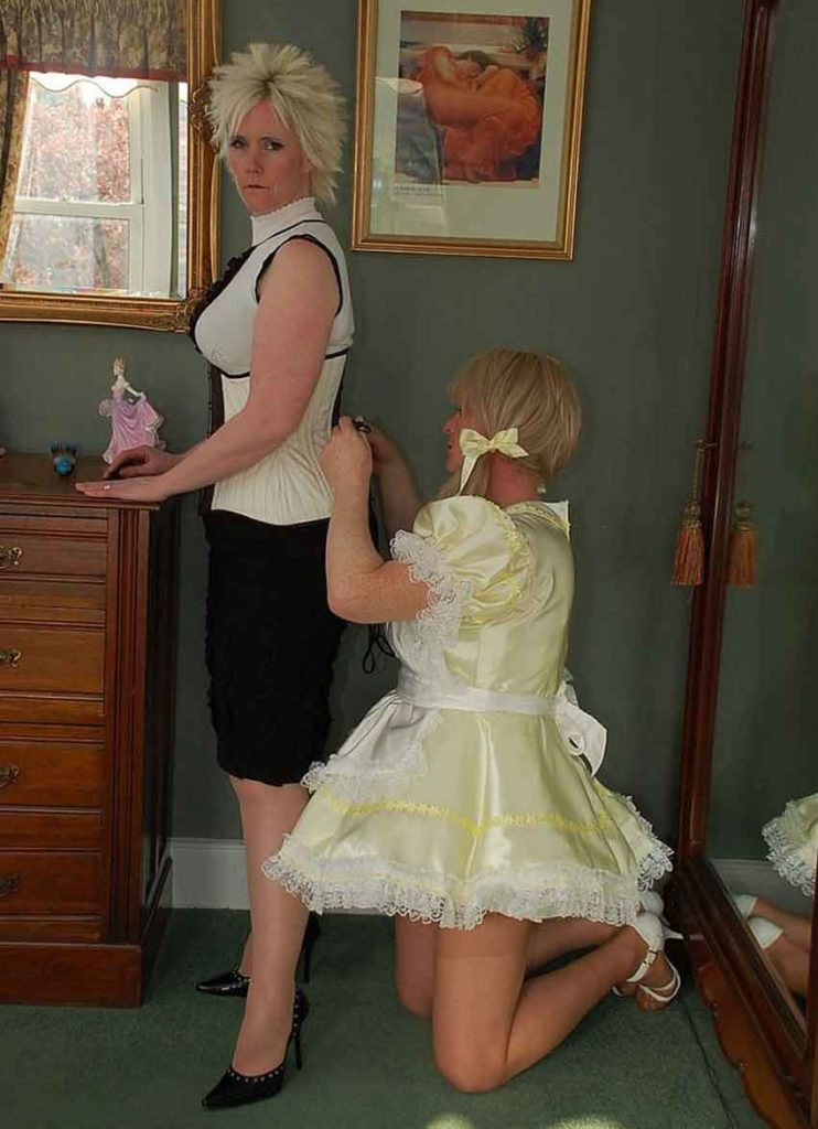 a mistress being zipped up by a sissy maid