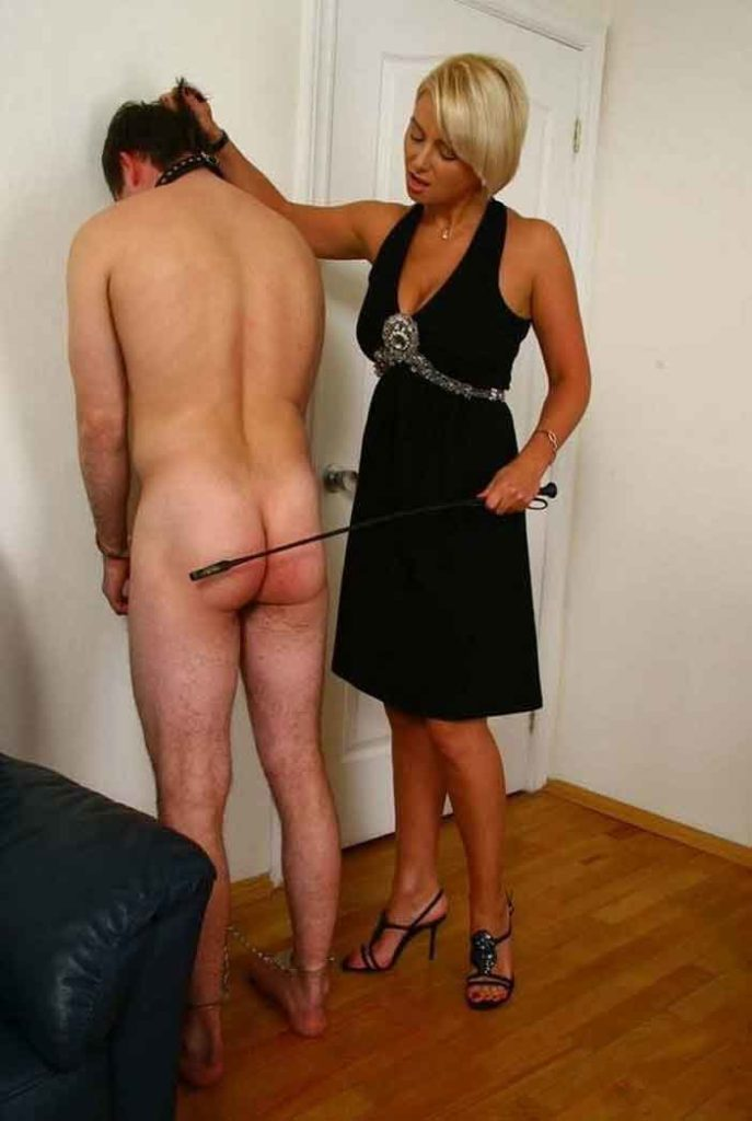 a mistress preparing to crop a naked sub bottom