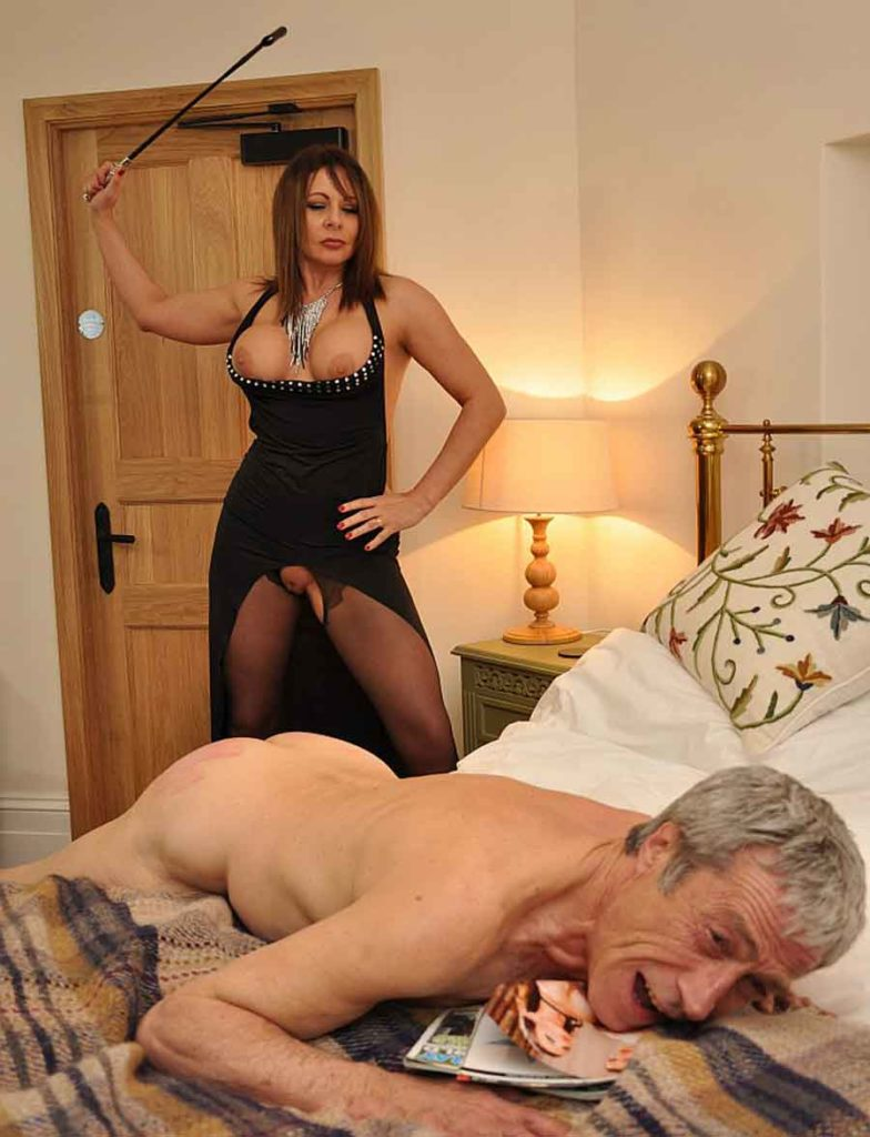 a mistress caning a naked slave on the bed