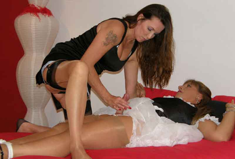 a slave in female clothing on bed with mistress