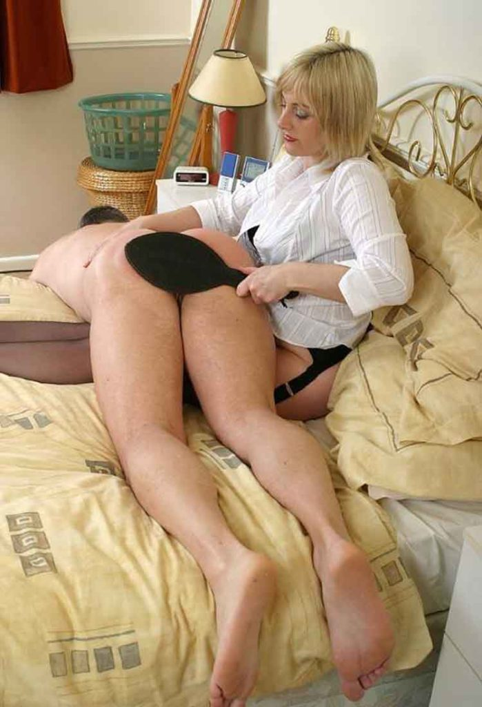 a mistress paddles a sub over her legs on the bed