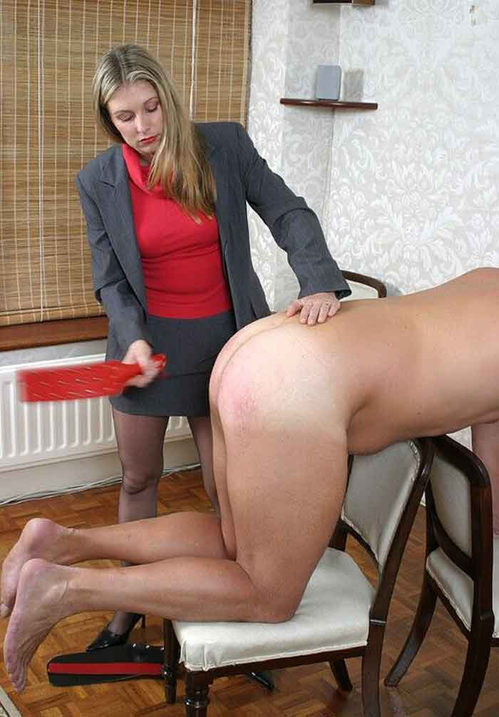 a mistress paddles a sub over a chair