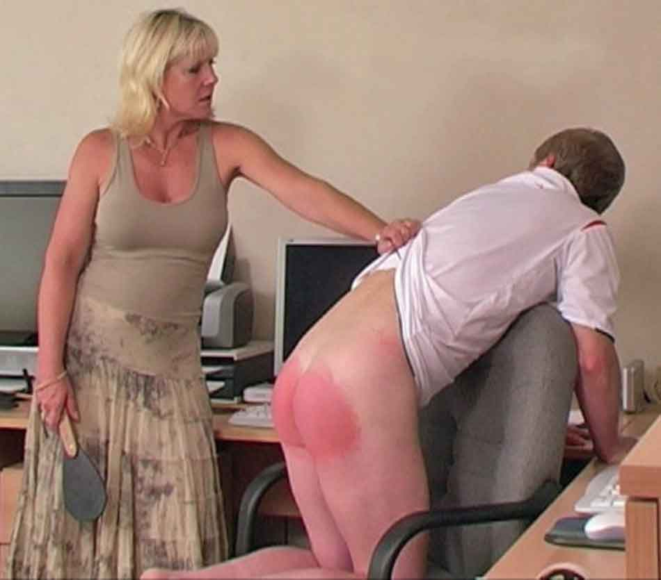 a mistress in the middle of a spanking with a paddle
