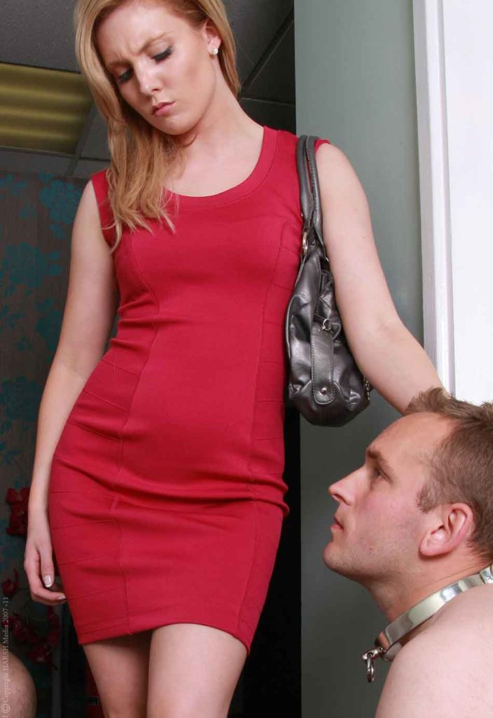 a mistress in red dress looks down on a sub