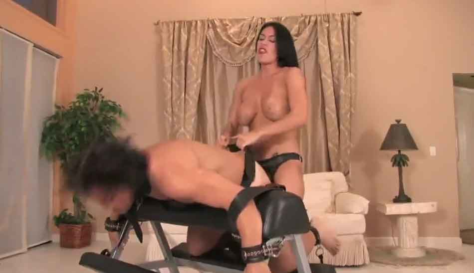 a mistress pegging her submissive on a bench strapped down
