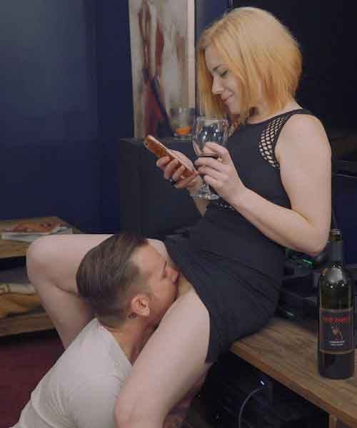 a woman on phone having oral sex given to her