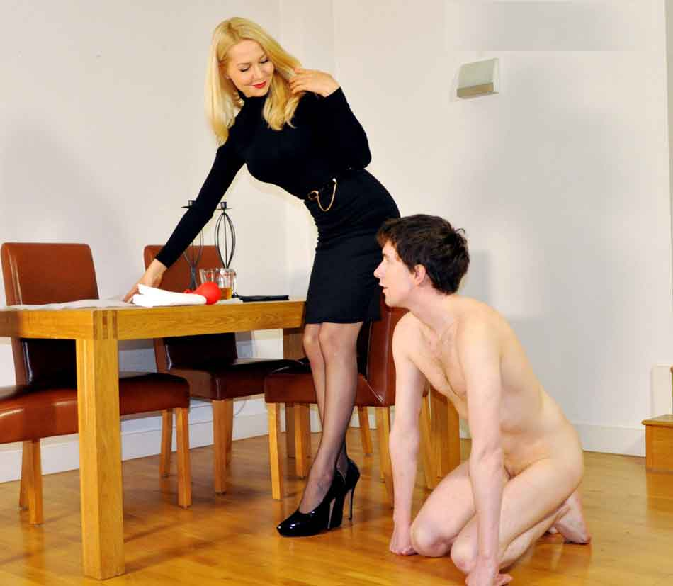 a woman at dest with kneeling naked sub
