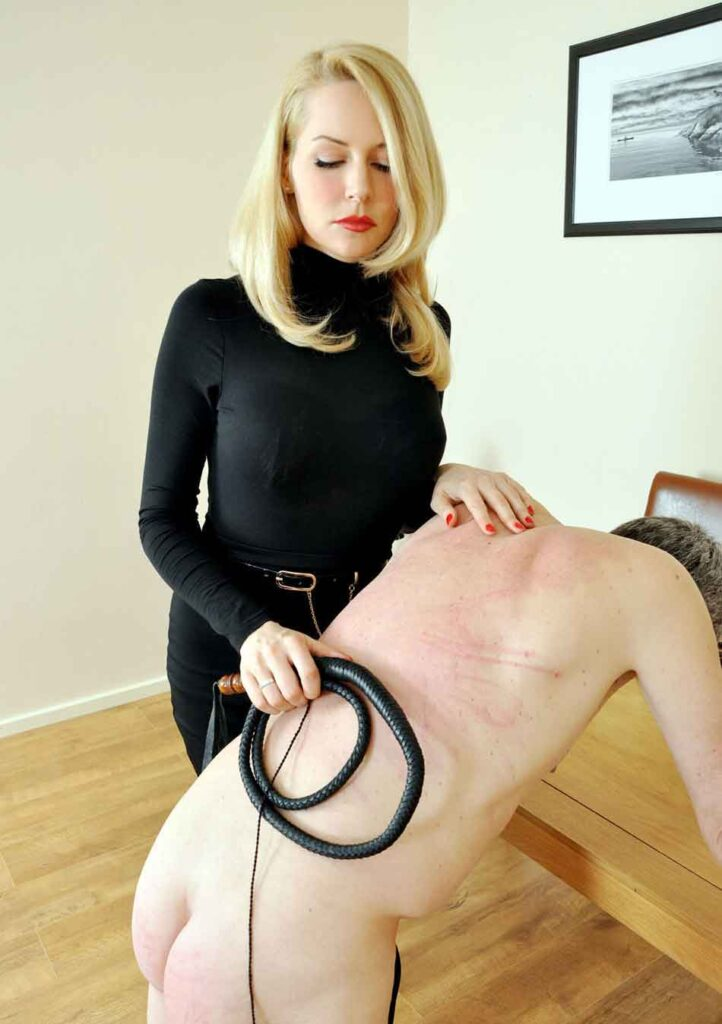 a mistress with a whip over a subs back