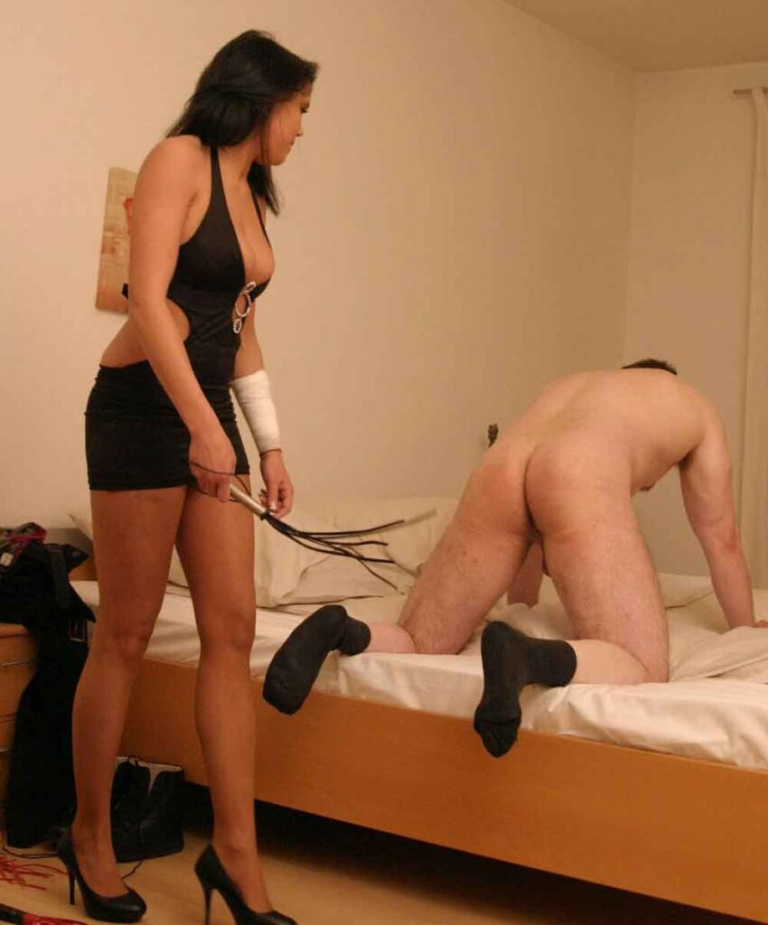 a mistress striking a bottom with a whip