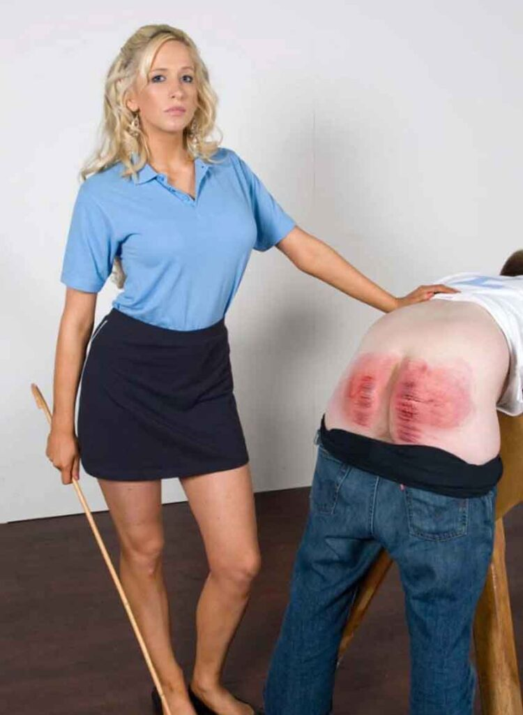 a mistress in a blue top bending a cane with sub