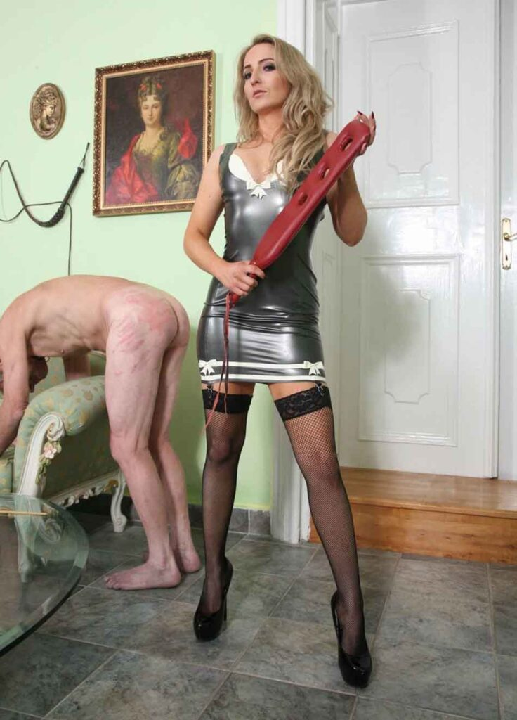 a mistress with a padlle and a sub over the couch