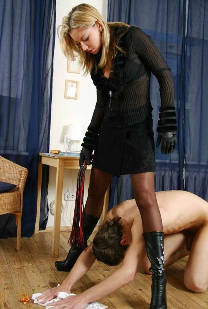 a mistress standing over a slave performing a chore on the floor