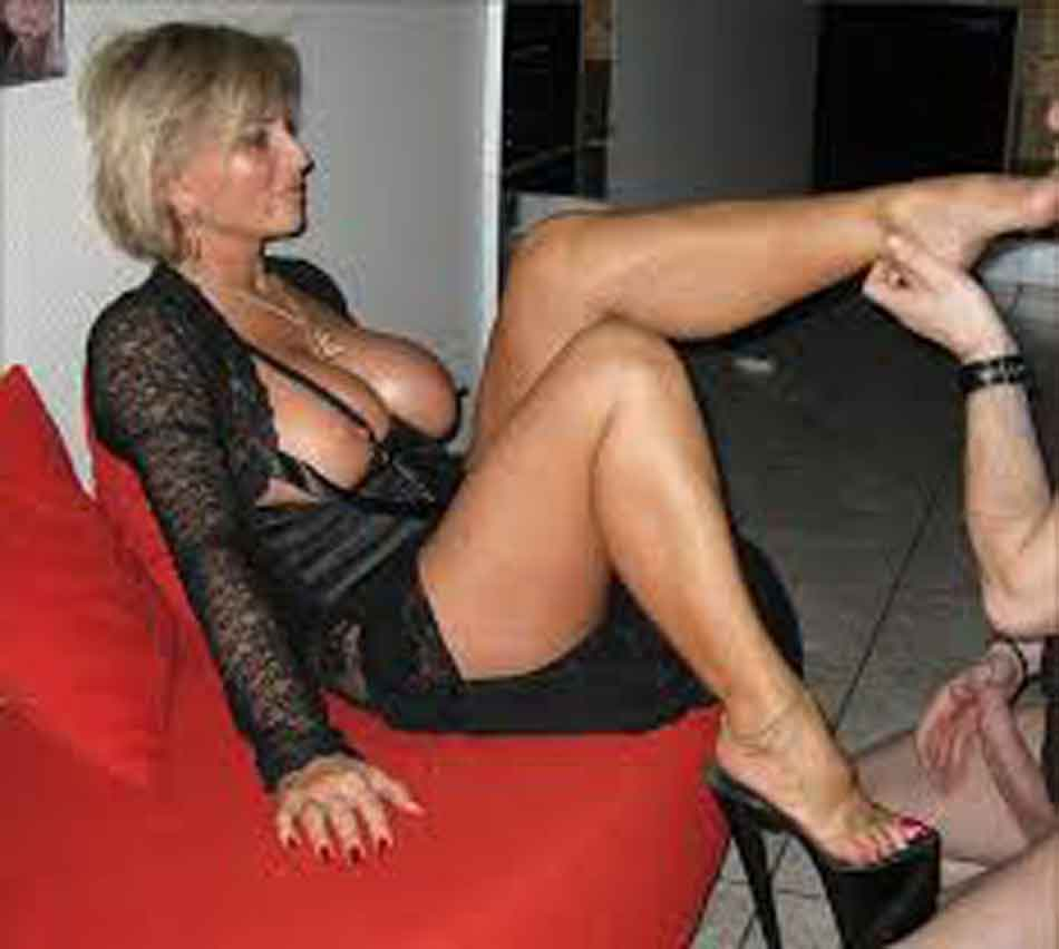 a mistress has her feet kissed while on couch