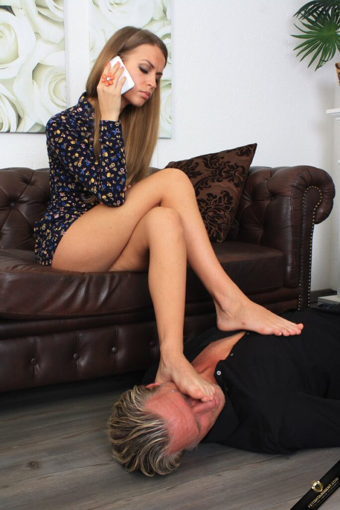 a mistress on phone with her foot on sub head