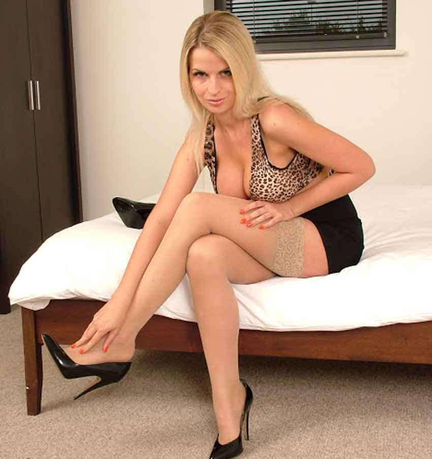 a mistress rubbing her feet on the end of the bed