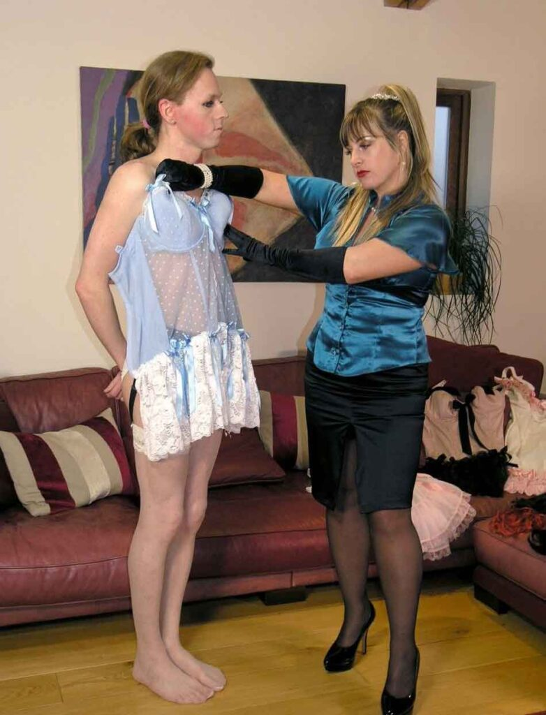 a mistress holding up a negligee to a feminized sub