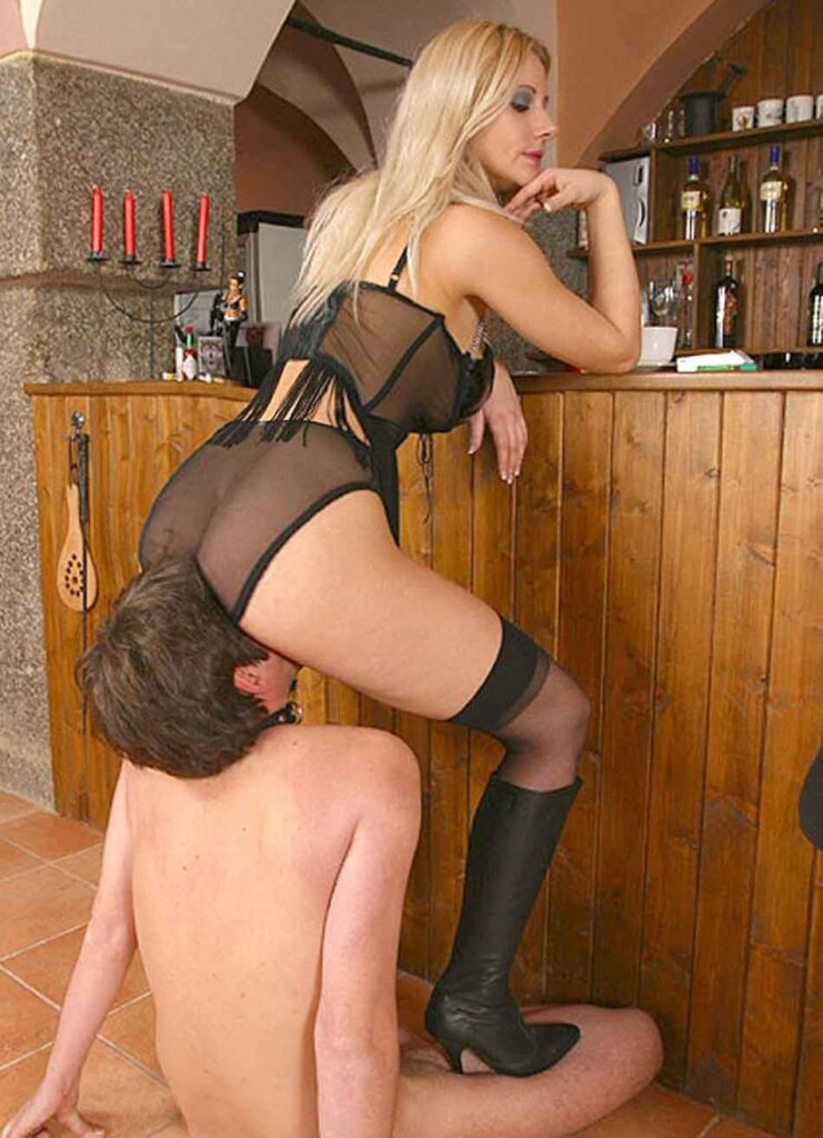 a mistress face sitting her submissive at a home bar