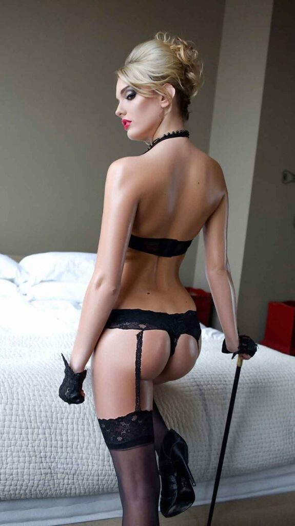 a mistress in lingerie looks very sexy by bed