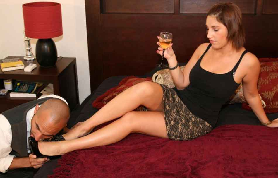 a mistress has her feet kissed on the bed