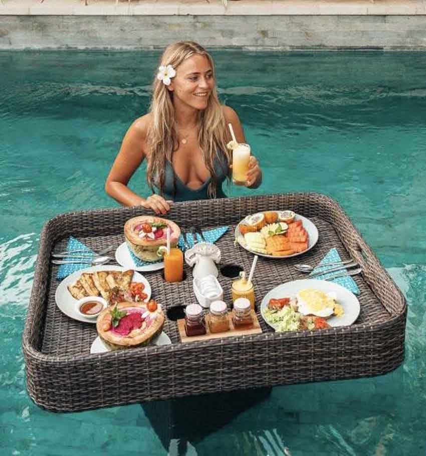 a mistress in the pool receivng breakfast floating