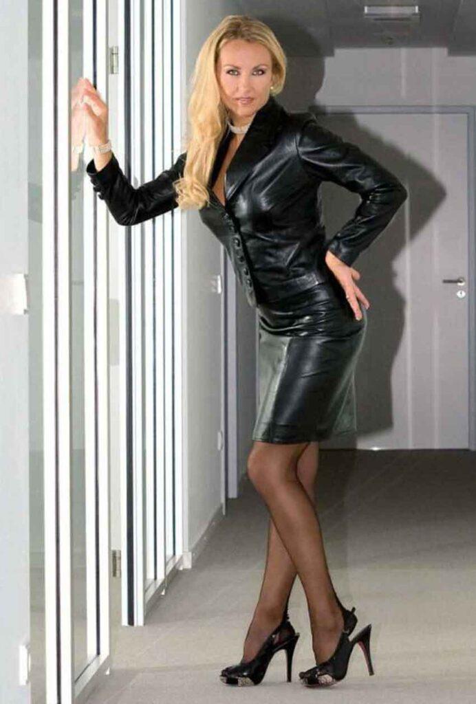 a mistress in black leather by window