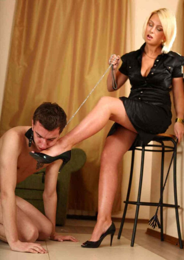 a mistress having her foot kissed with sub on leash