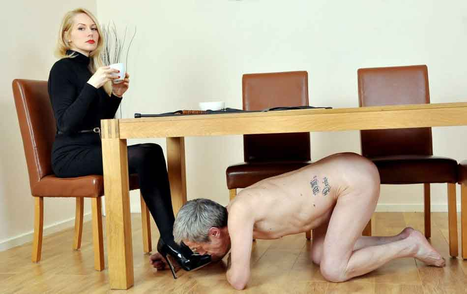a mistress having her foot kissed under breakfast table