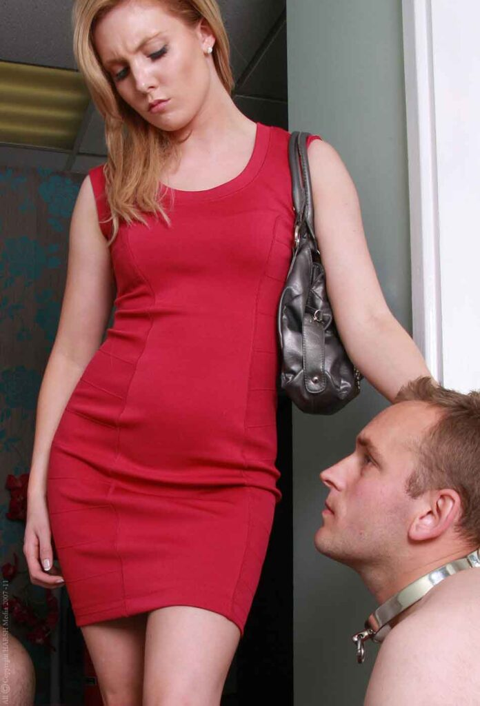 a mistress in red dress looking at kneeling sub