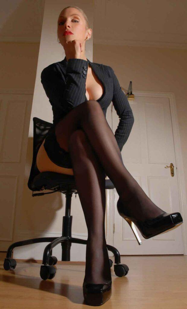 a mistress looking down cross legged on chair
