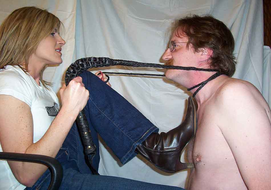 a mistress with leash pulling a sub close heel on chest