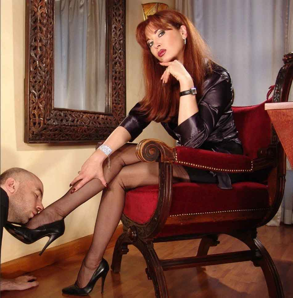 a mistress receives a foot kiss in chair