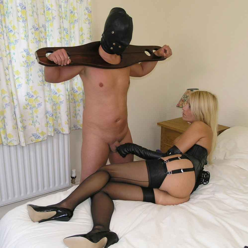 a mistress toys with sub penis in bed