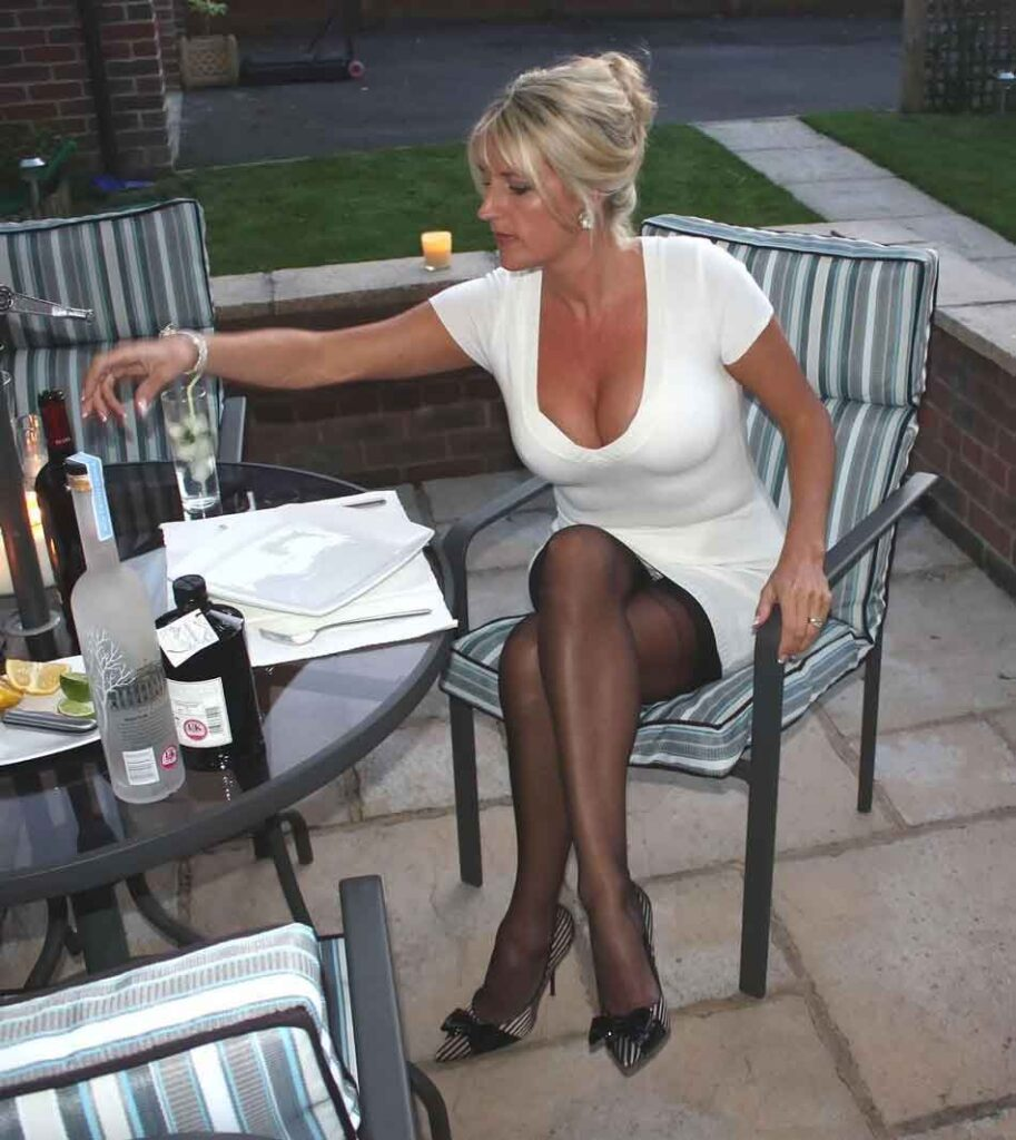 a mistress in white dress and stocking at outside table