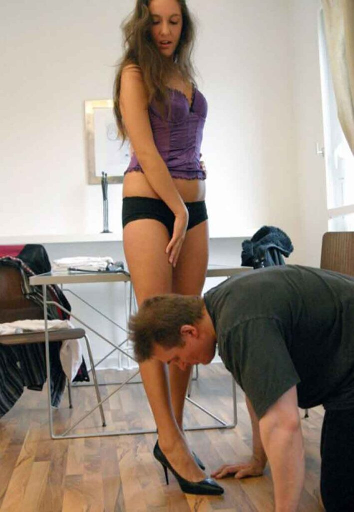 a mistress points at her feet to a sub