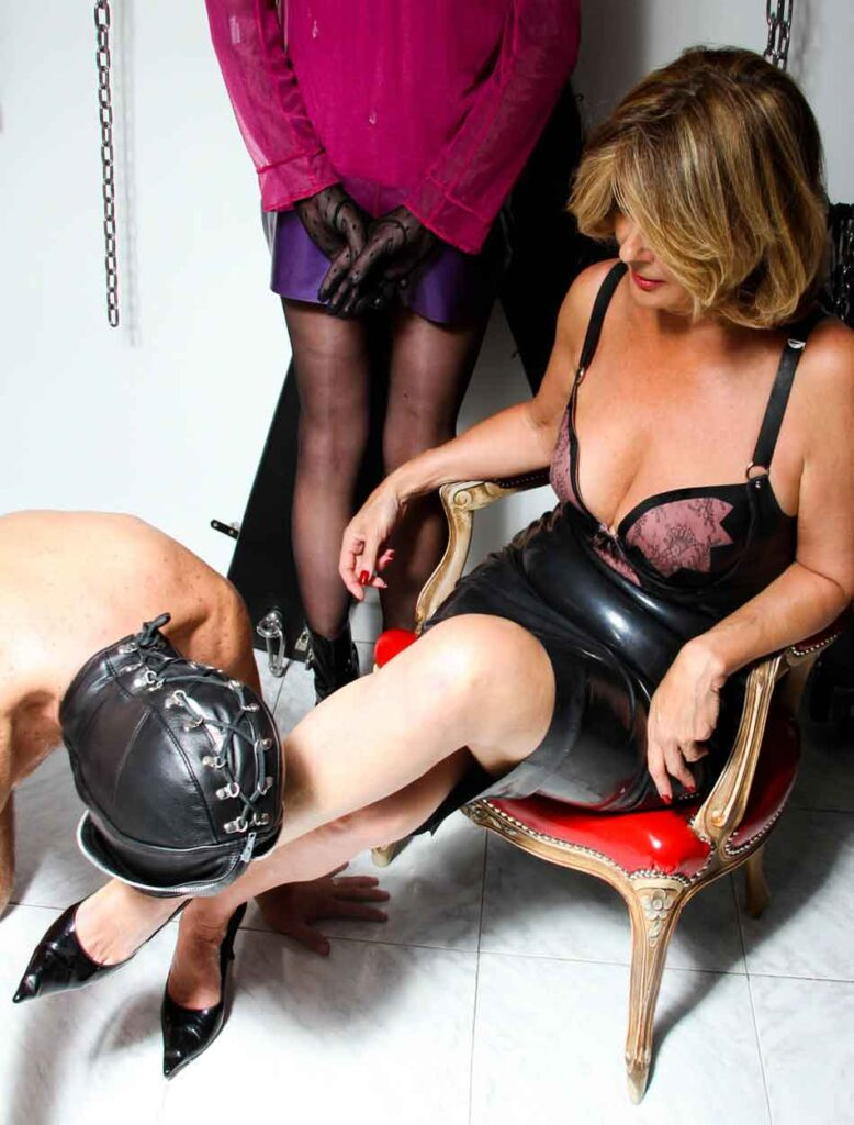 a mistress having her thigh kissed
