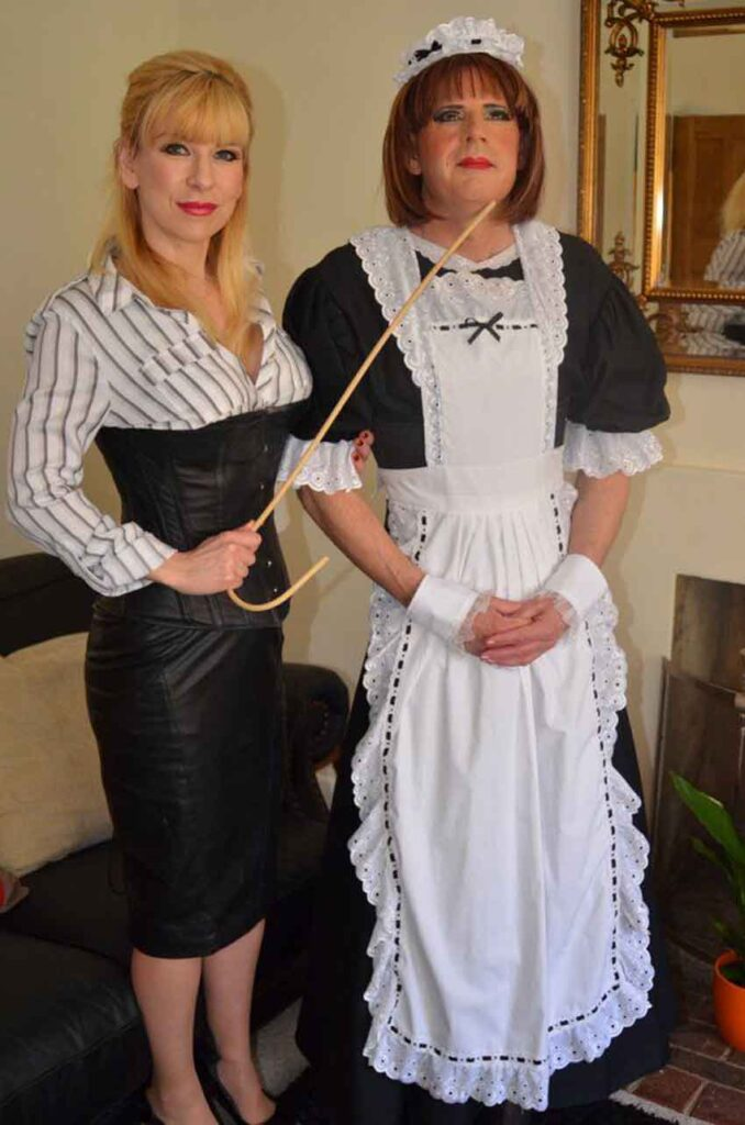 a sissy maid posing with mistress and cane