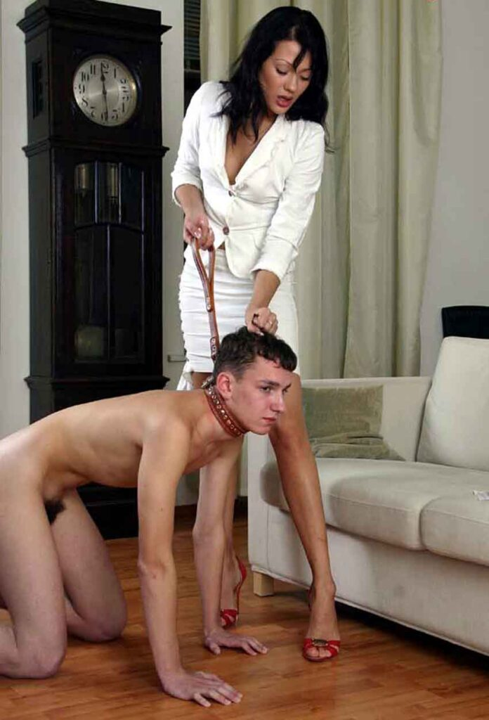 a mistress in white with a submissive on a collar