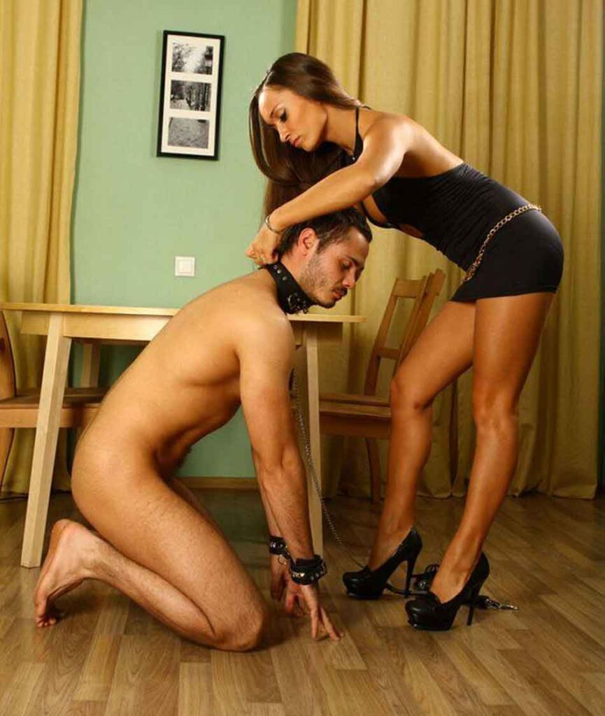 a mistress clasping a collar on a sub