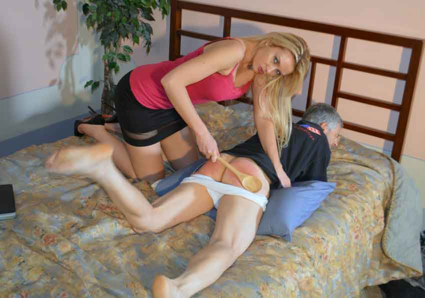 a mistress spanking a submissive on bed with a spoon