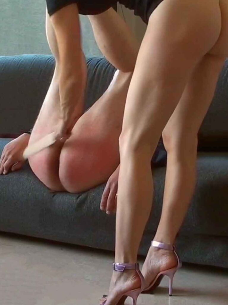 a mistress spanking a submissive on the couch with a paddle