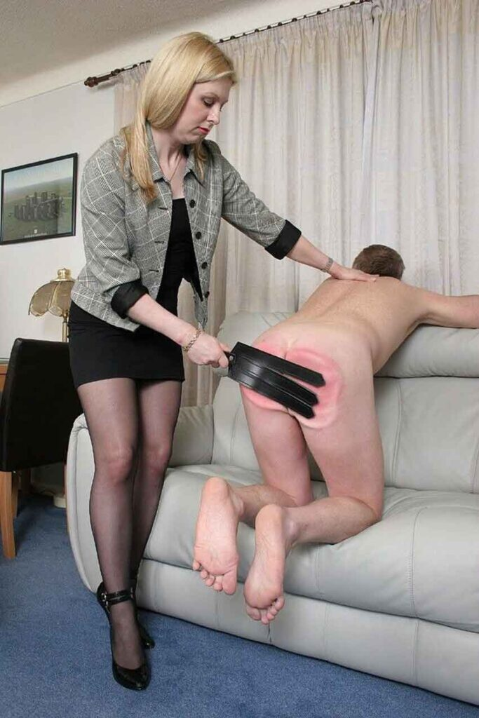 a mistress spanking a submissive with flogger