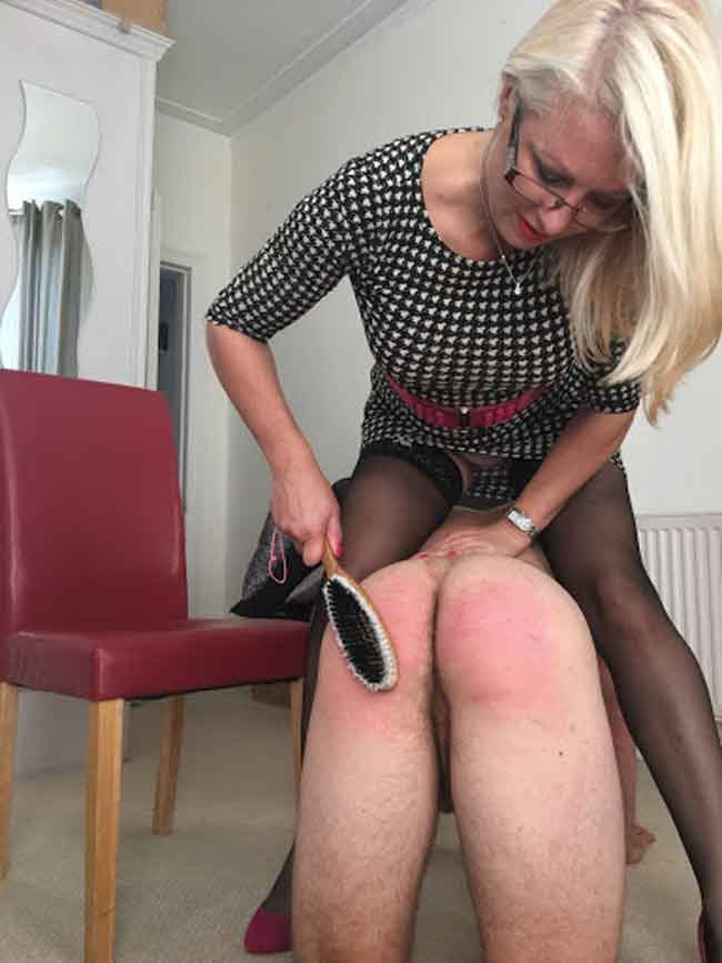 a mistress spanking a submissive with hairbrush