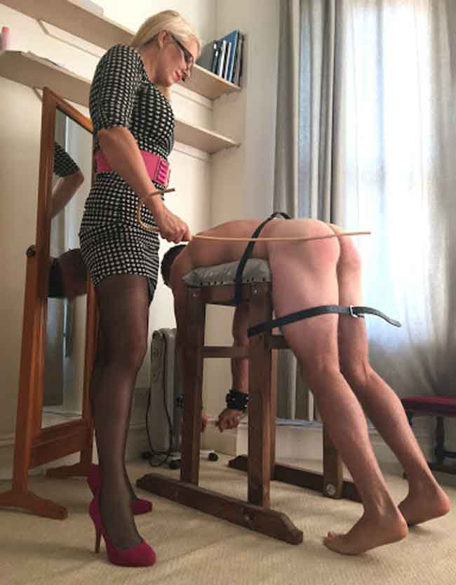 a mistress spanking a submissive strapped down