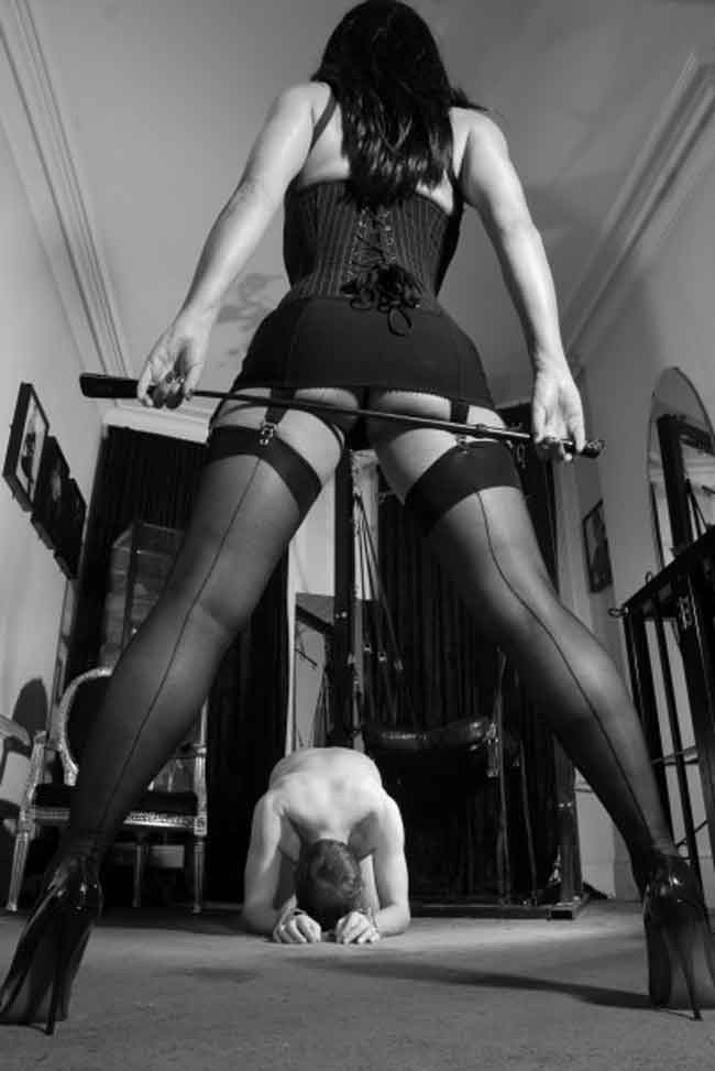 a mistress stands above her submissive