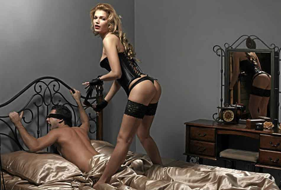 a dominant with her boyfriend on the bed with restraints