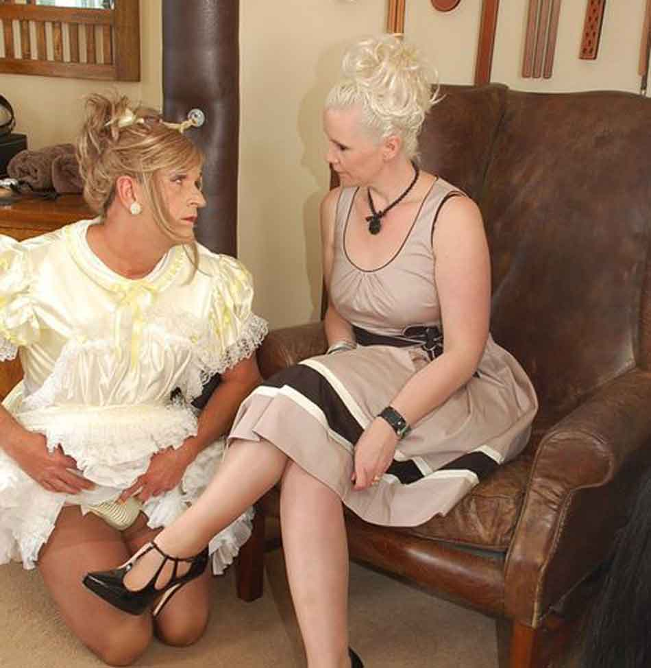 a sissy maid kneels next to her mistress